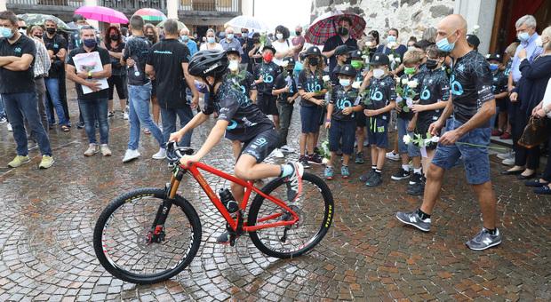 Le amiche di squadra in bici fuori dalla chiesa ai funerali di Petra