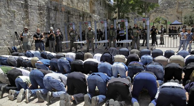 Musulmani pregano fuori dalla moschea di Al Aqsa sotto lo sguardo dei soldati israeliani